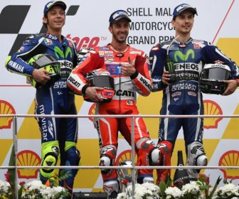 Ducati Team's Italian rider Andrea Dovizioso (C) poses on the podium after winning the 2016 Malaysian MotoGP at the Sepang International circuit on October 30, 2016 with second-placed Movistar Yamaha MotoGP's Italian rider Valentino Rossi (L) and third-placed Movistar Yamaha MotoGP's Spanish rider Jorge Lorenzo (R). / AFP PHOTO / MOHD RASFAN
